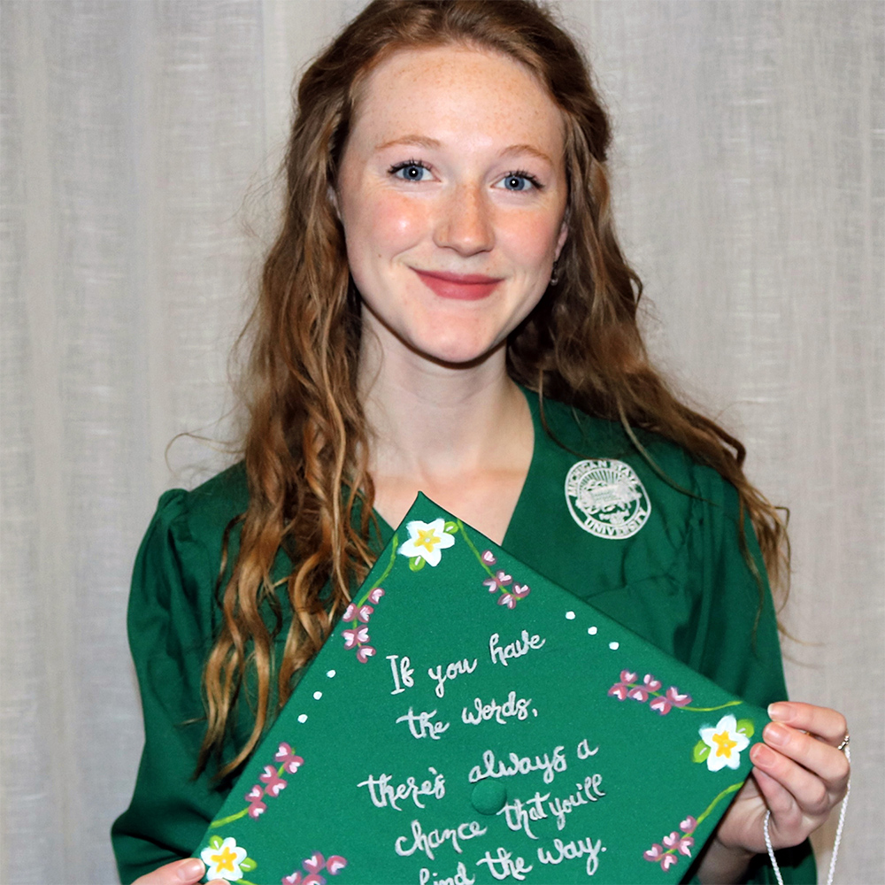 Young woman with long red hair in a graduation gown holding her cap
