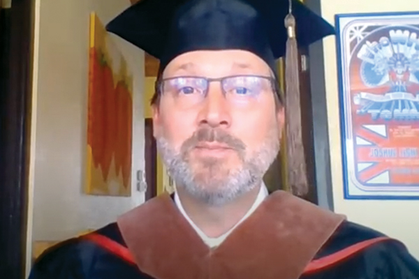 Man with beard and glasses wearing a cap and gown