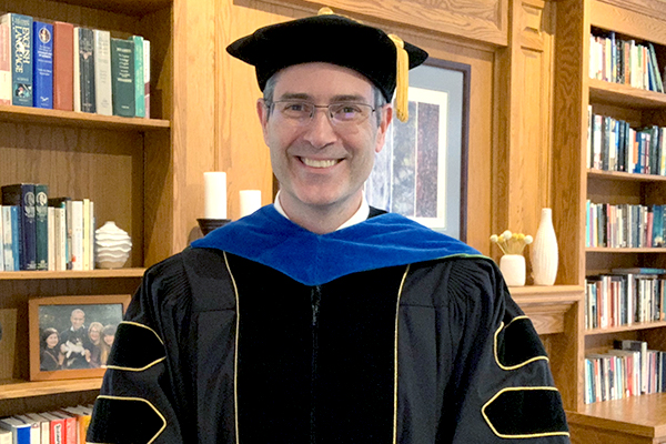 Man with glasses smiling in academic robes