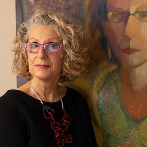 Woman with curly light blonde hair in front of a painting of a woman