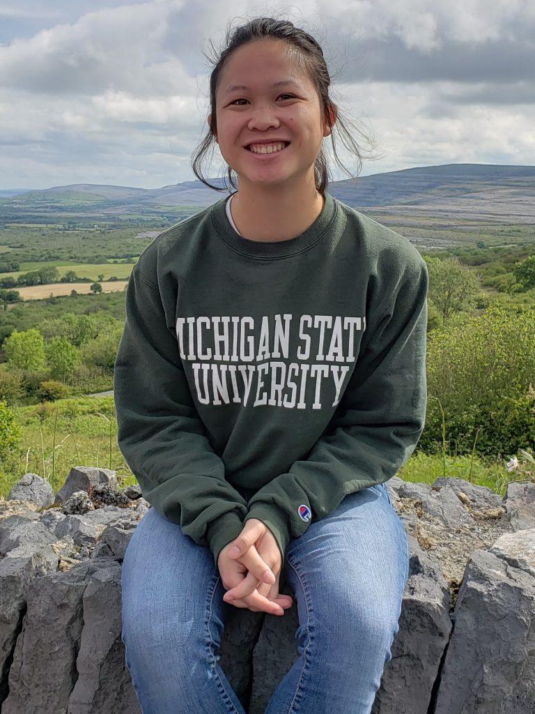 Young woman wearing a Michigan State University sweater sitting on a rock wall