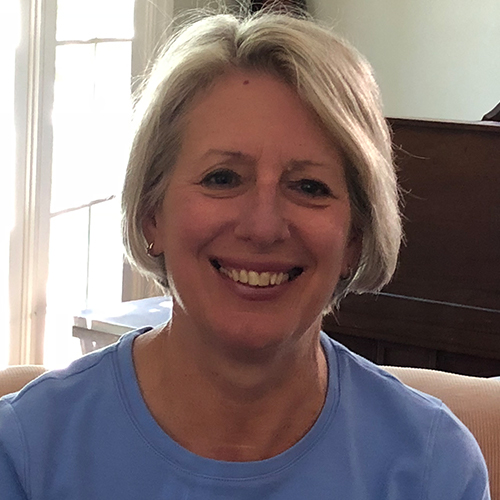 Smiling woman with short Grey hair wearing a blue shirt
