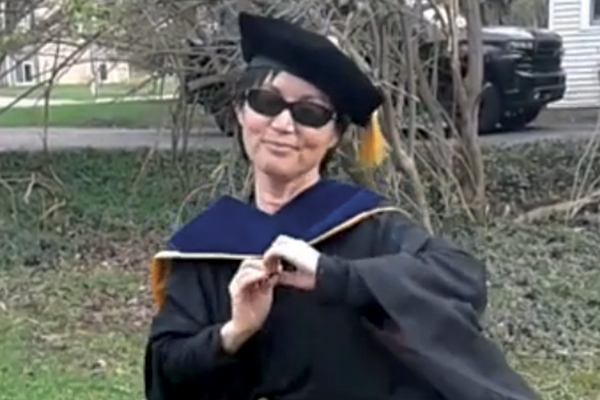 Woman with short dark hair and sunglasses wearing graduation regalia outdoors