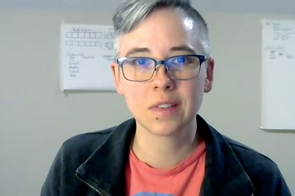 Person with short gray hair, glasses, and a pink shirt
