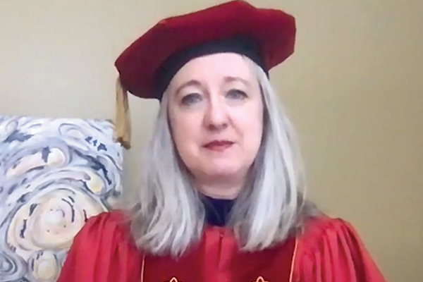 Woman with shoulder length grey hair in red academic cap and robes