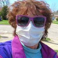 Woman in purple sunglasses and wearing a medical mask